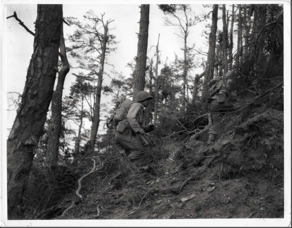 442nd Regimental Combat Team soldier moving into action in a hilly sector of France, Oct. 24, 1944, Bruyeres, France. Courtesy of the Seattle Nisei Veterans Committee and the U.S. Army